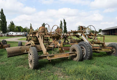 Grader on a trailer for heavy equipment. Trailer Hitch for tractors and combines. Trailers for agricultural machinery.