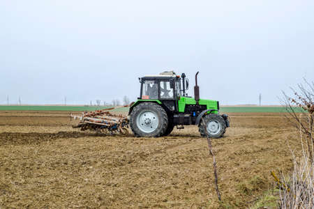 The field next to Krasnodar, Russia - March 18, 2018: Lush and loosen the soil on the field before sowing. The tractor plows a field with a plow.
