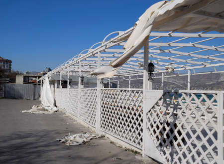 Consequences of the hurricane, torn awning from the gazebo. Garbage and aulitsa on the embankment. Stock Photo