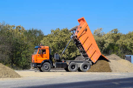The dump truck unloads rubble. The truck dumped the cargo. Sand and gravel. Construction of roads. Stock Photo - 98107923