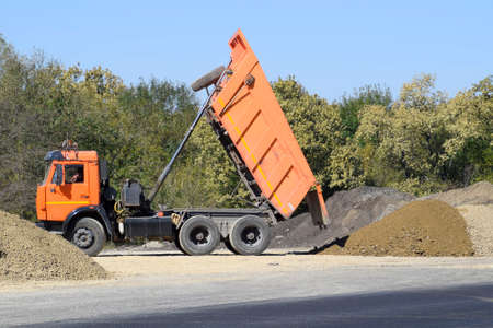 The dump truck unloads rubble. The truck dumped the cargo. Sand and gravel. Construction of roads.