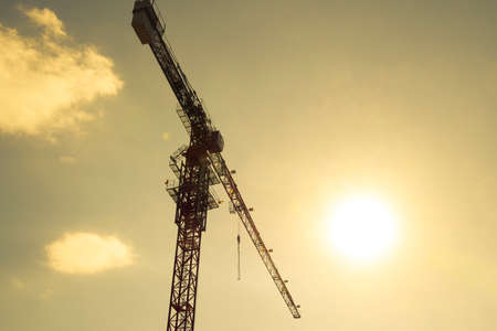 Construction of a new house. Tower building crane against the blue sky and sun. Construction of new buildings with a crane. Tower crane. Imagens - 98107944