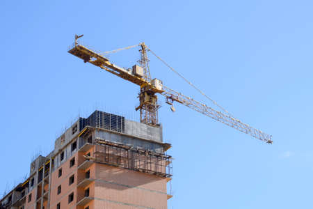 Construction of a new house. Tower building crane against the blue sky and sun. Construction of new buildings with a crane. Tower crane. Imagens - 98107946