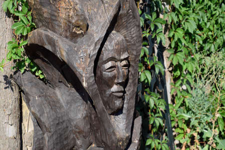 Wooden idol. Woodcarving. Mans face is carved on the trunk of a log