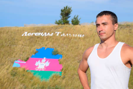 Ataman, Russia - September 26, 2015: man on the background of a hill with an inscription Legends of Taman and a tricolor of the Krasnodar Territory in the form of the territory of the Krasnodar Territory.