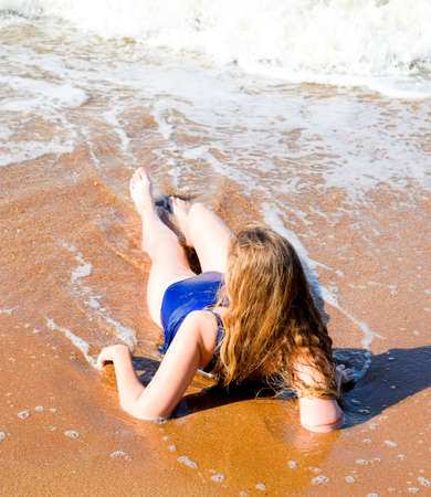Girl in a blue bathing suit lies on the seashore and relaxes. Waves caress the girls body.