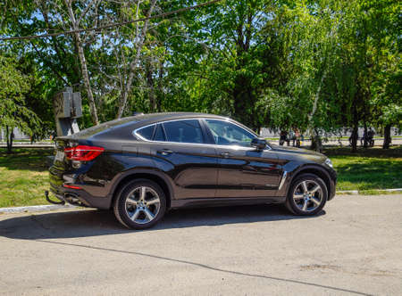 Slavyansk-on-Kuban, Russia - May 1, 2017: Black BMW X6 is parked in the park. A sports car of a premium class.