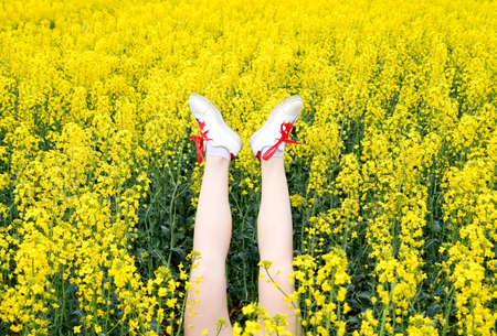 Female legs in sneakers sticking out of flowers. Legs up. Legs against the background of yellow rape blossoms. Foto de archivo