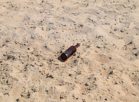 An empty bottle of beer is lying on the sand. Stock Photo