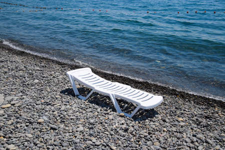 Chaise lounge is white on a stony beach by the coastline. Chaise lounge by the sea. Standard-Bild