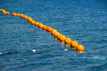 Orange buoys on a rope in the sea. Fencing for swimming in the sea. Imagens