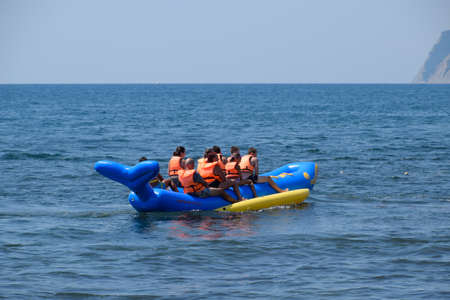Novorossiysk, Russia - August 06, 2018: A group of children on an inflatable boat at sea. Children in life jackets.