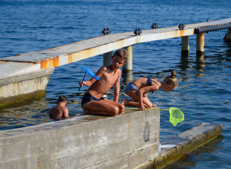 Novorossiysk, Russia - August 06, 2018: Children catch a net of small fishes in sea water.