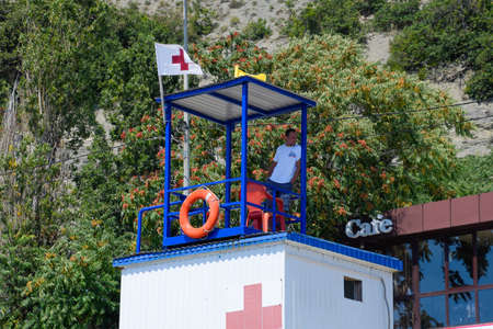 Novorossiysk, Russia - August 06, 2018: The rescuer on the rescue tower observes the shore. Novorossiysk beach. 에디토리얼