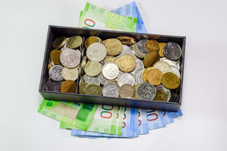 Coins of different denominations in a piggy bank box. Paper rubles under the piggy bank. New banknotes of Russia.