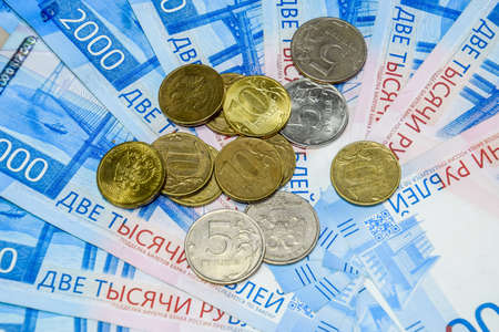 Russian banknotes and coins. A handful of coins on new Russian banknotes in denominations of 2000 and 200 rubles
