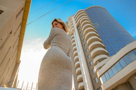 高いビルの近くでグレーのドレスを着た美しい姿の少女