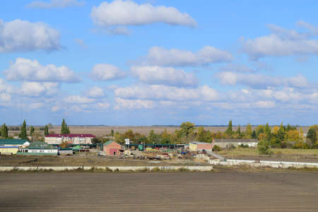 A view from above of a small Russian village. Rural landscape. Field and village. A semi-abandoned village