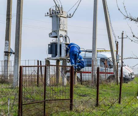 Krasnodar, Russia - March 23, 2018: Electricians repair electrical transformer. Repair team on the road