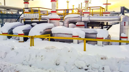 Node of valves on oil pipelines. Stop valves in the snow. Reducers on the valves