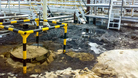Spilled oil on sandy soil near pipelines and process equipment. Oil leaks during operation and repair Imagens
