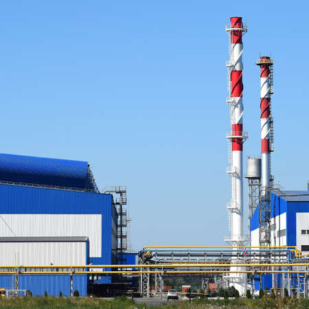 Big plant for processing scrap metal. Huge factory old metal refiner. Blue roof of the factory building. Exhaust pipes, radiators, cooling industrial units as well as office buildings. Stock Photo