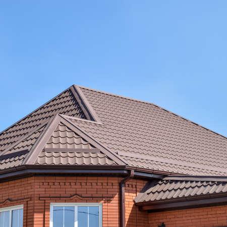 Einfamilienhaus mit einem Dach aus Stahlblech. Dachbleche. Moderne Arten von Dachmaterialien. Standard-Bild