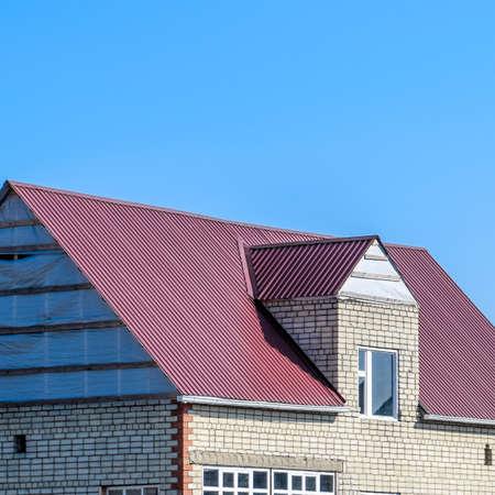 Haus aus Betonblock. Das Haus mit Plastikfenstern und einem Dach aus Wellblech. Überdachung der wellenförmigen Metallprofilform auf dem Haus mit Kunststofffenstern.
