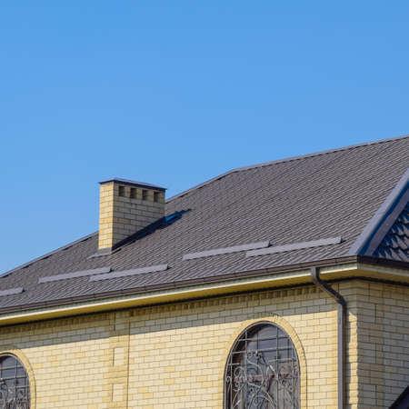 Dom z żółtej cegły i brązowego falistego dachu wykonanego z metalu. Kraty w oknach Zdjęcie Seryjne