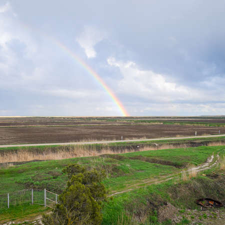 Rainbow, a view of the landscape in the field. Formation of the rainbow after the rain. Refraction of light and expansion in terms of spectra. Stok Fotoğraf - 121887289