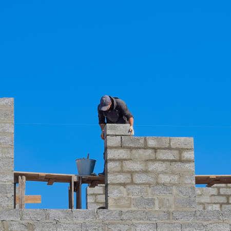 Le constructeur construit le mur de la maison à partir du parpaing. Ouvrier sur le chantier