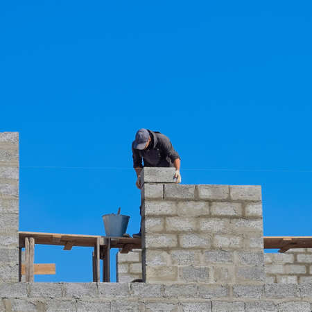 The builder builds the wall of the house from the cinder block. Worker at the construction site
