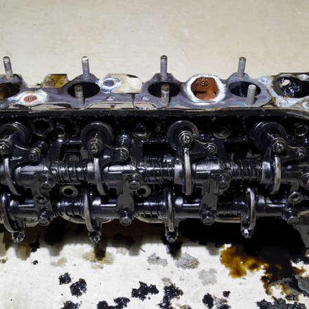 La tête du bloc de cylindres. La tête du bloc de cylindres retiré du moteur pour réparation. Pièces dans l'huile moteur. Réparation de moteur de voiture dans le service.
