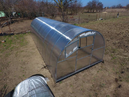 Polycarbonate greenhouse assembled from parts, prefabricated greenhouse. Greenhouse for vegetables. Stock Photo