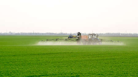 Tractor with high wheels is making fertilizer on young wheat. The use of finely dispersed spray chemicals. Tractor with a spray device for finely dispersed fertilizer. Standard-Bild - 120202334