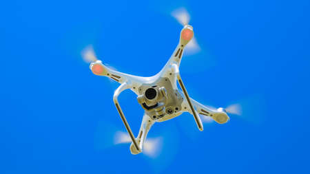 Quadrocopter against the blue sky with white clouds. The flight of the copter in the sky.