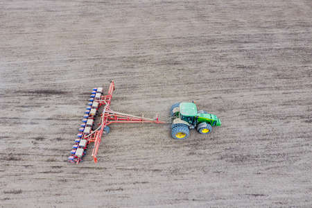 Sowing of corn. Tractor with a seeder on the field. Using a seeder for planting corn Stock fotó