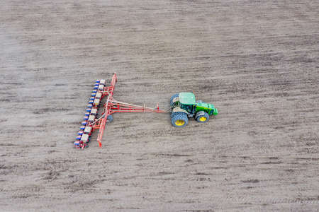 Sowing of corn. Tractor with a seeder on the field. Using a seeder for planting corn