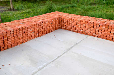 The red brick folded neatly on the foundation of the house. Home construction. Reklamní fotografie