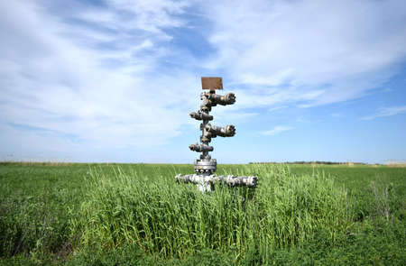 Canned oil well against the sky and field. Equipment of an oil well. Shutoff valves and service equipment. 免版税图像