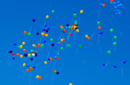 Palline multicolori, piene di elio, volano nel cielo azzurro.
