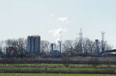 The smoke from the chimney of the plant. Industrial facility with a smoking pipe.