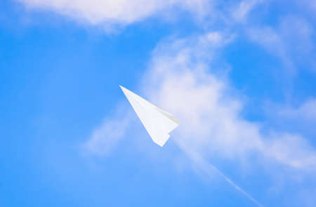 White paper airplane in a blue sky with clouds. The message symbol in the messenger.