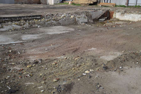 The ruined foundation of an old building, the walls of the basement of a demolished building and debris. Фото со стока