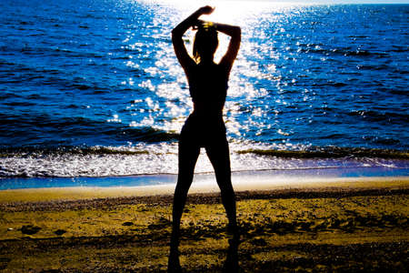 Silhouette of a beautiful girl figure on the background of the sea at sunset.