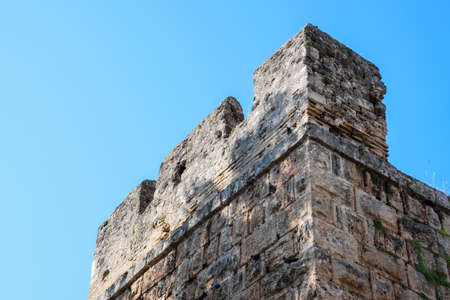 The wall near the gate of Hadrian, the texture of the stone walls of ancient stone blocks. Hadrians Gate, Antalya landmark. Ancient construction of the Gate of Hadrian