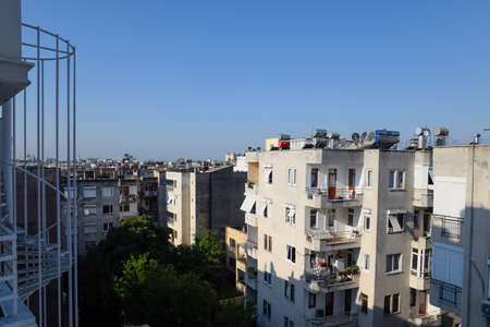 Antalya, Turkey - May 19, 2019: High-rise buildings in Antalya with barrels for water heating on the roof and sun blinds on the windows.