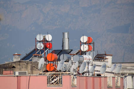 Antalya, Turkey - May 19, 2019: Steel barrels of boilers with water on the roof of a building to heat water. Water heating by the sun and solar panels.