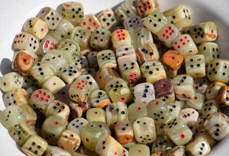 Dice made of green stone. Bowl with dices. Stock Photo - 124529063