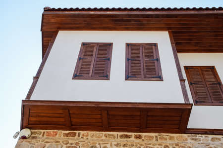 Ancient house with wooden shutters on the windows. City Kaleici in Turkey. Stock Photo - 124529075